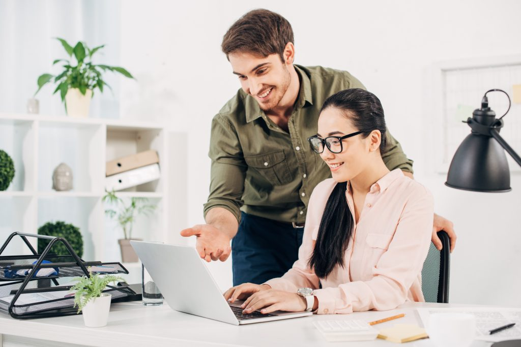 Two people smiling at laptop