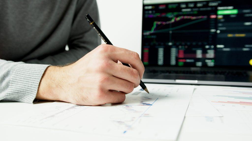Man writing on printed chart