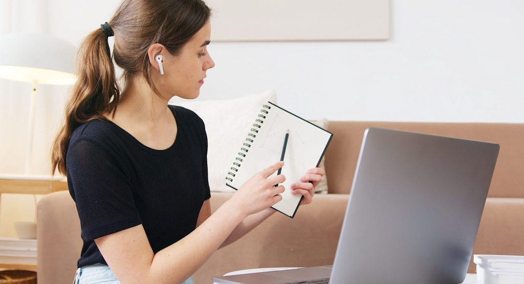 Focused woman using laptop while attending online webinar
