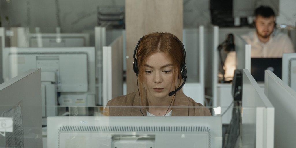 Woman in brown shirt wearing black earbuds