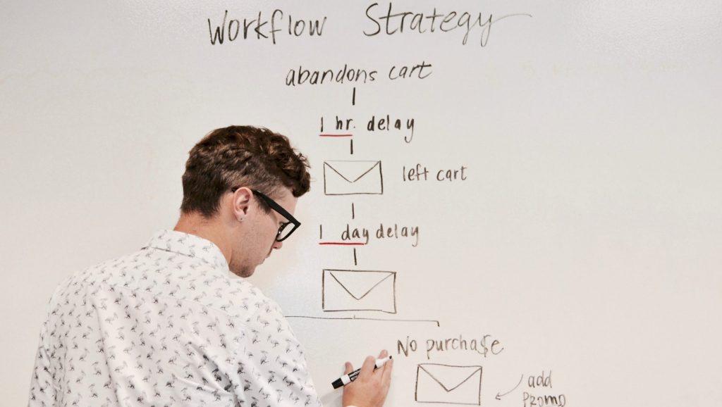 man writing on white board