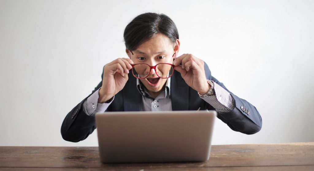 Amazed formal male looking at laptop screen