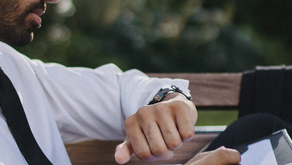 A man in a white long sleeves looking at his watch