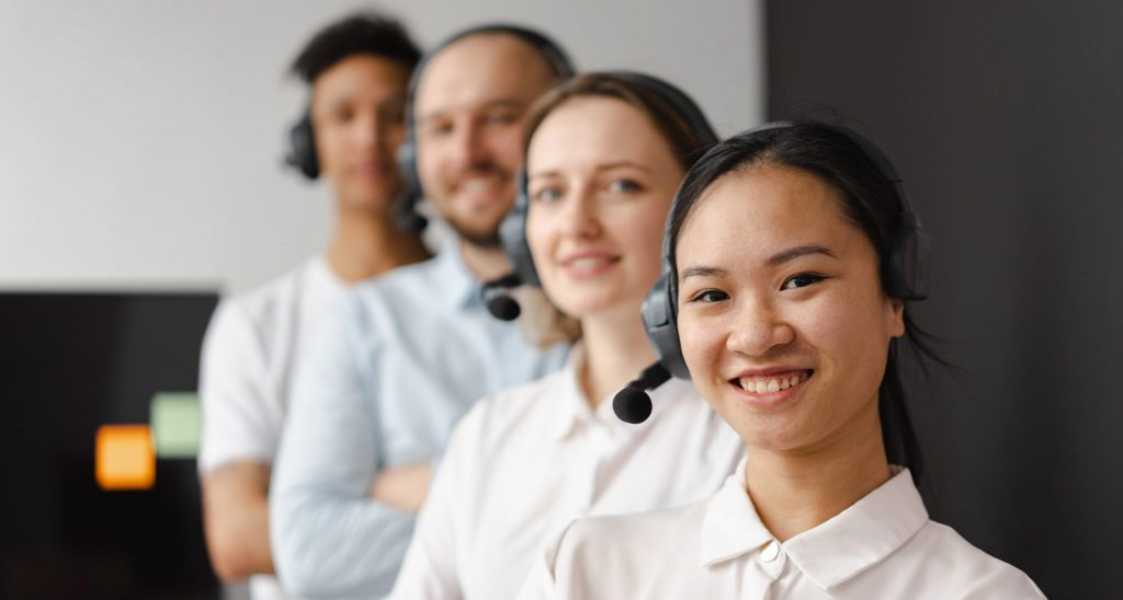 Call center agents smiling while looking at camera
