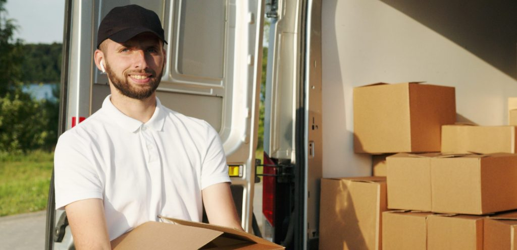 Man smiling while holding a box