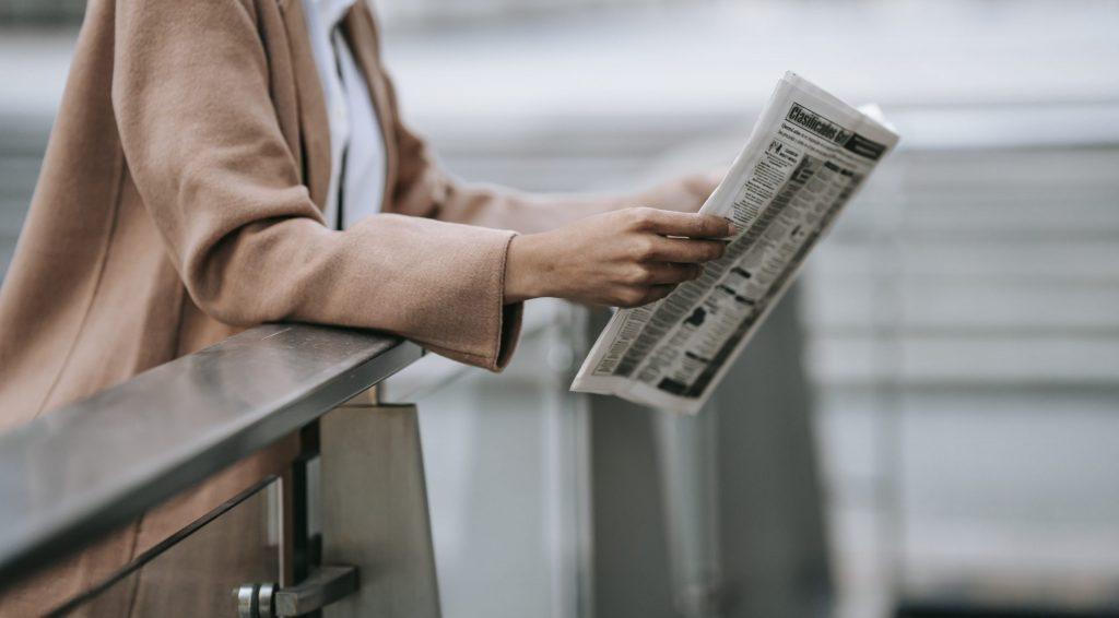 Unrecognizable black woman reading newspaper